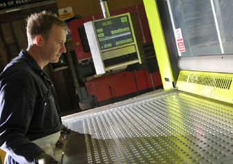 SB Components worker feeding sheet metal into machine