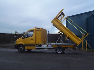 Raised hydraulic tipper in yellow